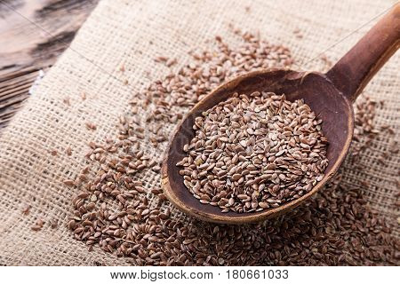 The seeds of flax are scattered on the table on a linen napkin. Seeds in a wooden spoon. Horizontal photo