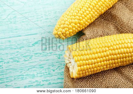 sweet corn on sackcloth half of corn some corn peeled some do not closeup with space for text