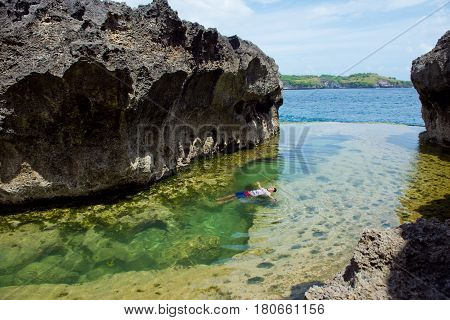Angel's Billabong Nusa Penida Indonesia - March 9 2017: A man rests in a natural pool with water on the background of the ocean.