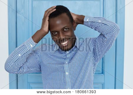 Portrait of attractive dark-skinned man holding hand behind scratching his head smiling seductively pleased with compliment. African American model posing at blue door backgroundkeeping hands up crossed behind his neck.