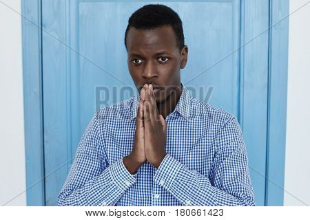 Praying young African American man in blue shirt. pressing hands together having upset look asking for forgiveness hoping for better times. Studio shot at blue door background.