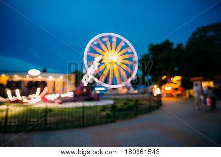 Abstract Motion Blur Image Of Brightly Colorful Illuminated Ferris Wheel In Amusement City Park On Black Blue Evening Sky Bokeh Boke Background.