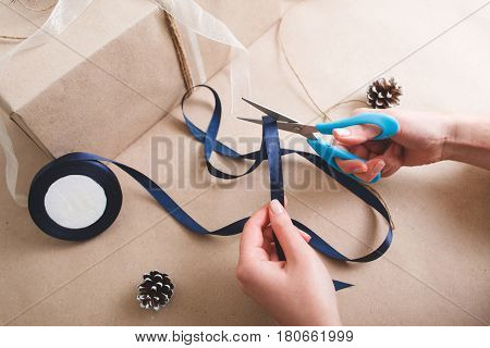 Packing presents for holiday, top view. Unrecognizable woman with scissors cut blue ribbon for wrapping the gift box.