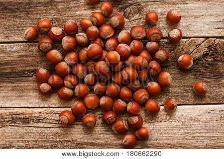 Heap of ripe hazelnuts on wood flat lay. Top view on wooden table with pile of filbert nuts, bright autumn background. Harvest, fall, food ingredient concept