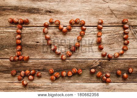 I love you from hazelnuts on wood flat lay. Top view on wooden table with love confession made of filbert nuts on rustic wooden background. Autumn, feelings, harvest concept