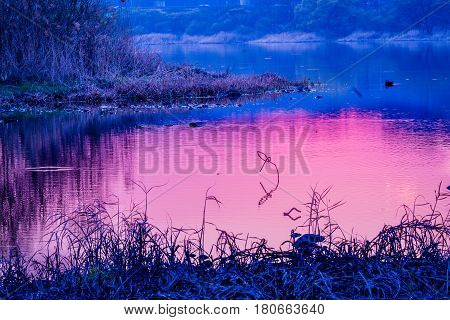 Bright reddish hue of setting sun reflected on the surface of river