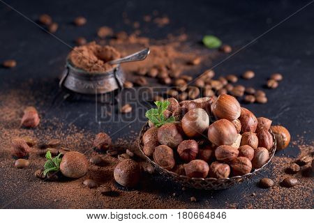 Hazelnut coffee beans and cocoa powder in dark background. Ingredients for cooking homemade chocolate sweets. Confectionery and sweets concept