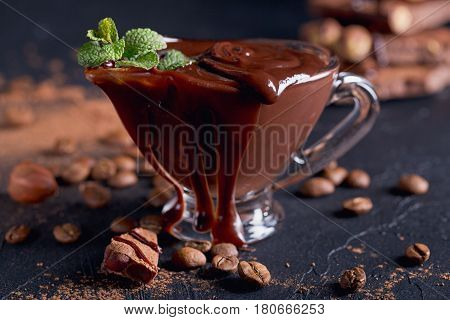 Homemade hazelnut spread or hot chocolate in glass bowl with nuts and chocolate bar. Nuts and chocolate background. Ingredients for cooking homemade chocolate sweets. Confectionery and sweets concept.