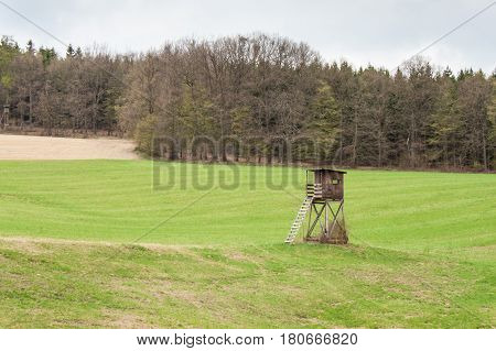 Hunting Tower on a field near the forest. Hunting deer. Overcast day