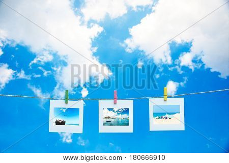 Vacation photos hanging on a rope background the sky
