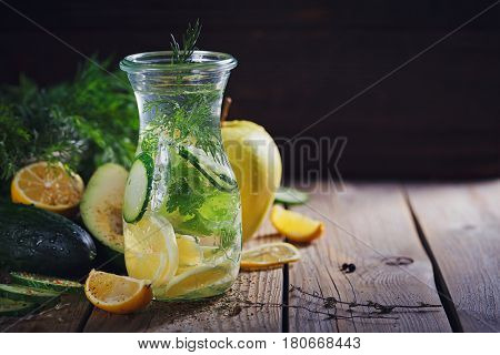 Background with assorted green vegetables: apple avocado cucumber lemon and detox water on rustic wooden table top. Healthy food detox dieting vegetarian and weightloss concept with copy space.