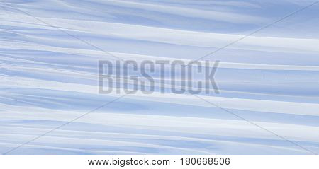 Soft Tulle fabric Background Texture with selective focus. Decorative Transparent white textile on the blue background. Beautiful Wide Horizontal Web banner