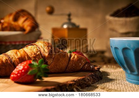 Closeup of a continental breakfast with croissant and a cup of milk and coffee grinder on background