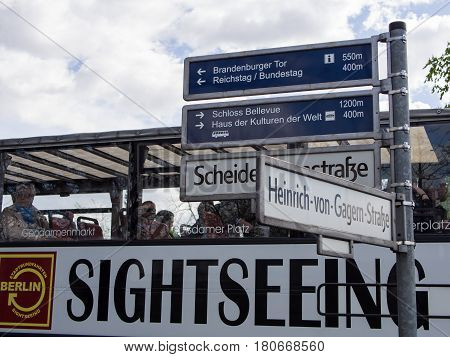 BERLIN GERMANY - APRIL 6 2017: Sightseeing Tourist Bus At A Sign Post Directing To Famous Sights In Berlin Germany