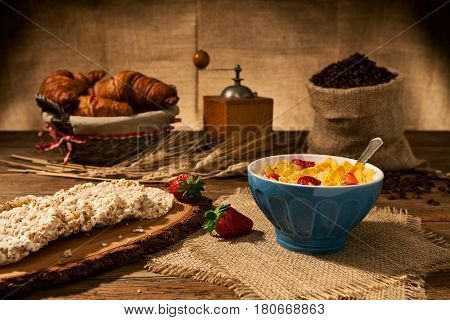 Continental breakfast with cornflakes and strawberries in a cup of milk and rice crackers over an old wooden table