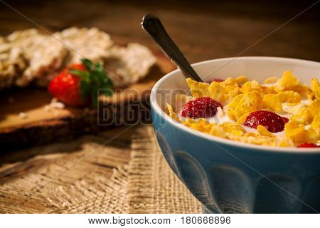 Closeup of a continental breakfast with cornflakes and strawberries in a cup of milk and rice crackers on background