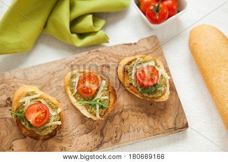 Fresh Homemade Crispy Italian Antipasto Called Bruschetta Topped With Tomato On Wooden Board
