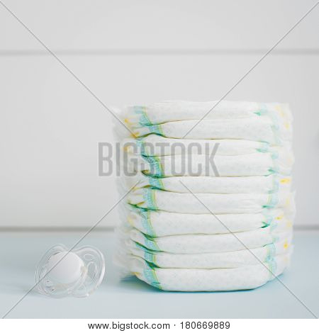 A stack of diapers against a white wardrobe. square