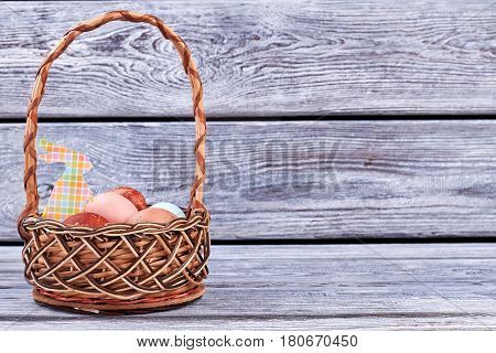 Easter basket, gray wood surface. Colorful paper rabbit cutout.