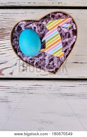 Easter gift box, wooden surface. Blue egg in shredded paper.