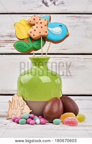 Easter sweets and plywood craft. Colorful biscuits in vase.