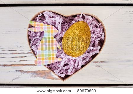 Box with shiny Easter egg. Light purple shredded paper. Make a special Easter present.
