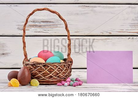 Blank paper and Easter basket. Candies on wooden surface.