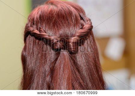Long brunette hair braided to a plait - closeup
