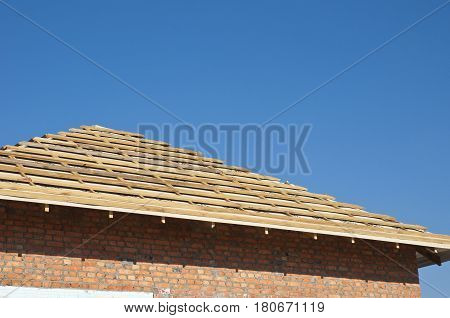 Outdoor Against a Blue Sky. Roofing Construction Exterior with Red Brick house Wall Facade.