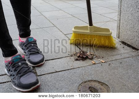 Street sweeper cleans with broom on citizen dough - close-up