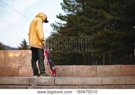 The boy is pondering standing with a skateboard