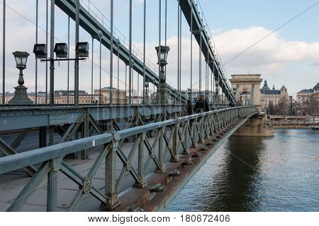 Budapest, Hungary - March 09, 2017: Sidewalk with tourists on the Szechenyi Chain Bridge over Danube river with view to Pest side