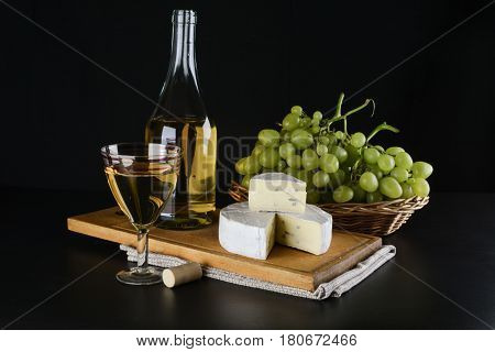 A bottle of white wine in the background grapes in a basket and cheese Dor Blue and a glass of white wine on a black background