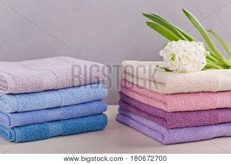 Two stacks of colorful bath towels with hyacinth flower on light background. Pastel colors cotton towels. Hygiene fabricspa and textile concept