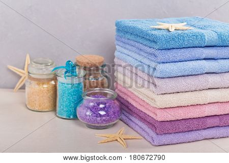 High stack of colorful bath towels with sea salt on light background. Pastel colors cotton towels. Hygiene fabricspa and textile concept