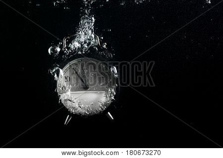 Alarm clock in water. Concept of time. Clock falls into the water with a splash and air bubbles. Plenty of space for text.