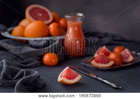 Glass of freshly squeezed grapefruit juice with fresh citrus fruits on dark background. Grapefruits oranges and tangerines