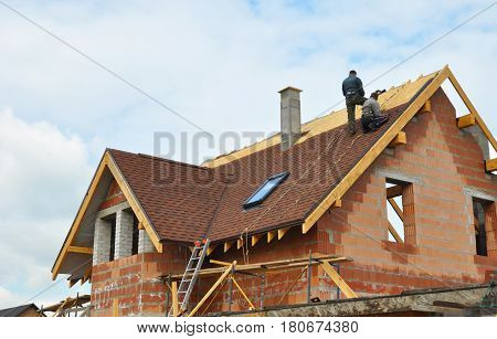 Roofing Construction and Building New Brick House with Modular Chimney Skylights Attic Dormers and Eaves. Asphalt Roofing Shingles Background. Roof Shingles - Roofing Construction, Attic construction, attic skylight, Roofing Repair.