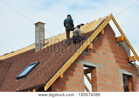 Roofing Construction and Building New Brick House with Modular Chimney Skylights Attic Dormers and Eaves Exterior. Roofers Install Repair Asphalt Shingles or Bitumen Tiles on the Rooftop Outdoor.