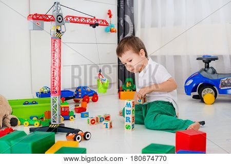 boy builds a tower of blocks on the floor