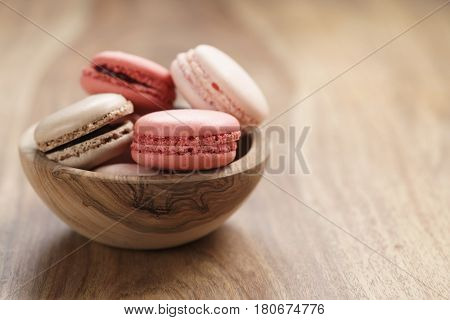 pastel colored macarons with strawberry, rose and caramel flavour in wood bowl with copy space