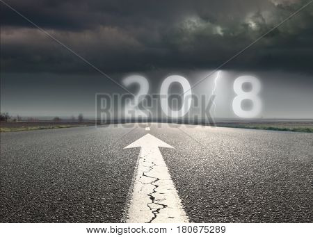 Driving on an empty road towards troublesome and uncertain new year 2018. Future and prediction concept.