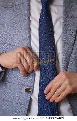 Unrecognizable businessman setting the tie straight - simple and clean, close up