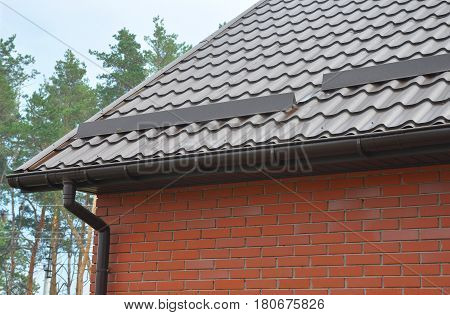 Closeup on New Rain Gutter System Downspout Draine Pipe and Roof Protection from Snow Board (Snow Guard) on House Metal Tiled Roofing Construction against Forest Background.
