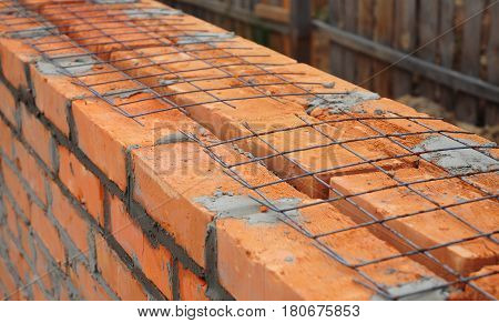 Close up on laying building bricks with iron grid to better wall strength. Building house wall. It is almost impossible to build brick walls that contain steel reinforcing bars.
