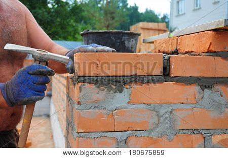 Bricklayer Using a Bricklaying Hammer to Build New Red Brick Wall Outdoor. Bricklaying Basics Masonry Techniques.
