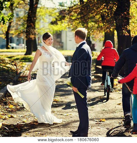 Bride Looks Happy Whirling In The Park Behind A Groom