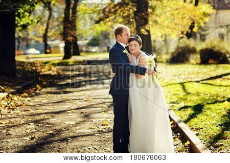 A Tender Picture Of Newlyweds Standing In The Bright Autumn Park