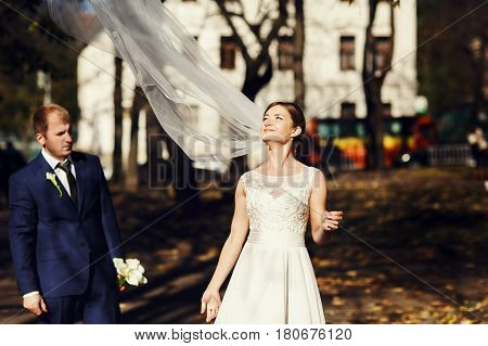 Wind Blows A Delicate Bride's Veil Up While She Stands With A Groom In A Park