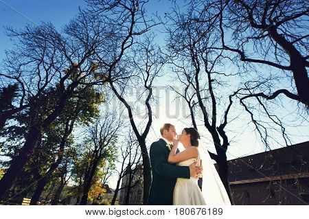A View From Below On A Weding Couple Standing In The Autumn Park
